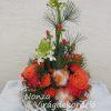 Téli asztaldísz narancs-fehér színű virágokkal