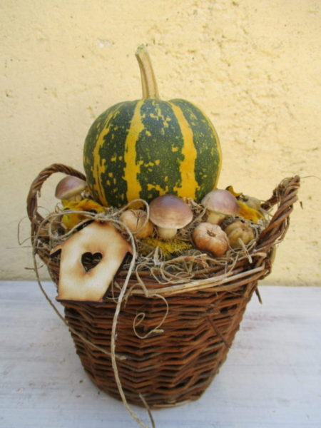 Őszi asztaldísz fonott kosárban, tök díszítéssel, házikóval
