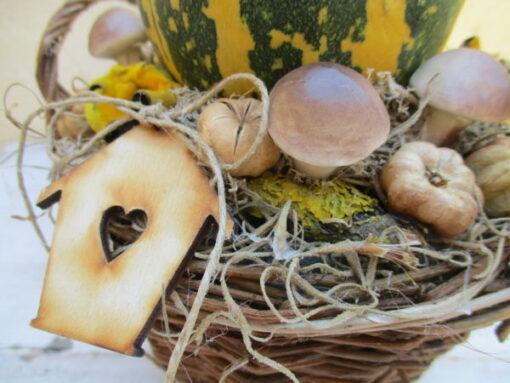 Őszi asztaldísz fonott kosárban, tökkel díszítve, házikóval