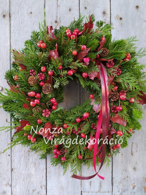 Piros téli ajtókoszorú örökzöld alapon, természetes díszítéssel